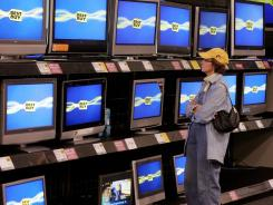 A customer browses TVs at a Best Buy.