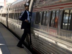 A conductor steps back onto the train after making a stop at the Amtrak station in Wilmington, Del.
