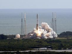 A rocket with NASA's Curiosity rover aboard clears the tower during launch.