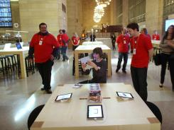 People walk through the new Apple store in Grand Central Station in New York City. The store is scheduled to open to the public on Friday.