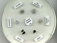 This undated handout photo provided by NASA shows a six-inch lunar sample disk containing three rock pieces and three clumps of lunar dirt.