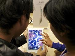 Shoppers try the front camera of the iPad 2.