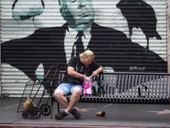 A man sits beneath a portrait of Alfred Hitchcock on Hollywood Boulevard in L.A.