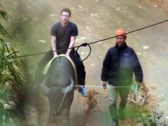 Facebook's founder and billionaire Mark Zuckerberg touring a village on a buffalo walked by a farmer at the popular mountainous tourist site of Sapa, in northern province of Lao Cai.