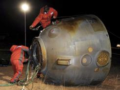 Technicians prepare to move the re-entry capsule of the Shenzhou 8 spacecraft Nov. 17 in Siziwang Banner in China's Inner Mongolia Region.