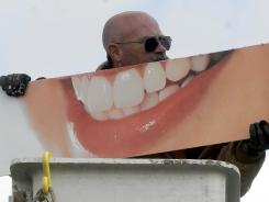 Steve McQuistion, an employee of Sign Affects,  hangs a dentist sign at the Tower Building in Springfield, Ohio.