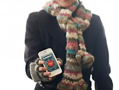A woman poses with a smartphone displaying the Winter Survival Kit.