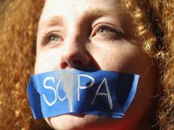 Protester Nadine Wolf demonstrates against the proposed Stop Online Piracy Act (SOPA) and Protect IP Act (PIPA) outside the offices of U.S. Sen. Charles Schumer (D-NY) and U.S. Sen. Kirsten Gillibrand (D-NY) on January 18, 2012 in New York City.