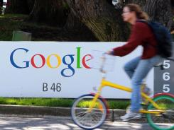 A bicyclist rides by a sign at Google headquarters in Mountain View, Calif.