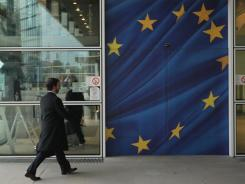 A glass door decorated as the flag of the European Union at an entrance to the Berlaymont building of the European Commission in Brussels, Belgium.