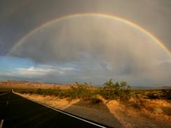 A rainbow forms over State Highway 178 between Death Valley National Park and Shoshone, Calif.