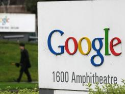 A pedestrian walks by a sign at Google headquarters in Mountain View, Calif.