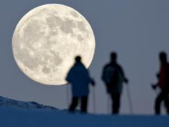 Catch this month's full moon on Feb. 7. Here, three snowshoe hikers look at a full moon behind the Weissfluhjoch mountain in Arosa, Switzerland.