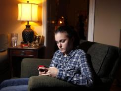 Taylor Smith checks her Twitter feed while posing for a photograph at her home in Kirkwood, Mo.