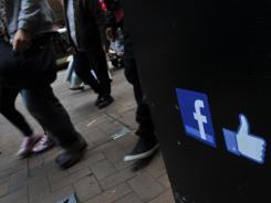 People walk by a Facebook logo in Hong Kong.