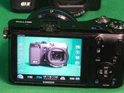 A Canon G1X reflected in the viewfinder of a Samsung NX200.