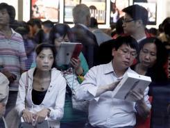 الزبائن الصينية تعلم استخدام 2 باد داخل متجر أبل بكين.