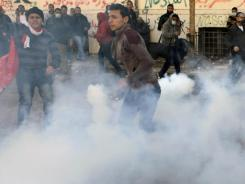 A protester throws away a tear gas canister Feb. 5 in Cairo. The Anonymous movement claims to have hacked Combined Systems, a U.S. tear gas company that has sent shipments to Egypt.