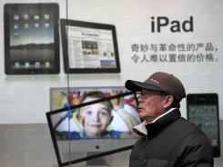 A man stands near Apple's iPad advertisement in Shanghai, China.