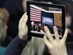 A person uses an iPad to make a video as New Jersey Gov. Chris Christie addresses a crowd in Voorhees, N.J., during a town hall meeting in January.