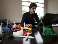 Rajeev Kulkarni, vice president and general manager consumer solutions at 3D Systems Corporation, works at his desk while surrounded by objects created on a 3-D home printer.