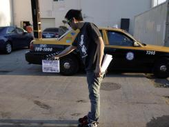 Crew member Arthur Hong holds a clapboard while filming holiday movie trailers at the Maker Studios in Culver City, Calif.