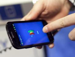 A person tries a smartphone loaded with Google Wallet.