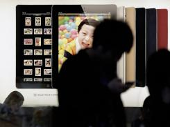 Customers look at Apple products in Shanghai, China.