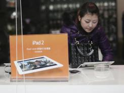 A customer tries out Apple's iPad 2 at a retail shop in Chongqing, China.