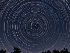 Circumpolar stars appear to rotate around the north celestial pole due to the Earth's rotation in this photo.