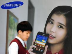 A South Korean high school student walks past advertising for the Samsung Galaxy S II LTE. The phone runs Android software.
