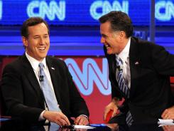 Former U.S. Sen. Rick Santorum and former Massachusetts Gov. Mitt Romney speak during a commercial break during a debate in Arizona.