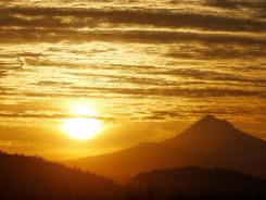 The sun rises over Mount Hood in Portland, Ore., on Thursday as the largest solar storm in five years engulfs the Earth. The storm arrived more peacefully than it could have, scientists say.