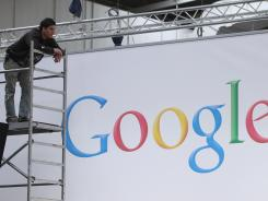 A worker pauses while preparing a Google stand at a technology trade fair.