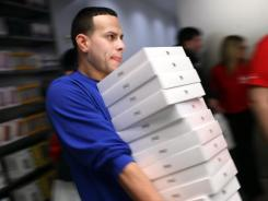 An Apple employee carries boxes of new iPad's as they went on sale around the world last Friday.