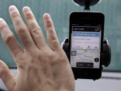 Ben Gleitzman waves his hand over traffic and navigation app Waze on his iPhone in Menlo Park, Calif.