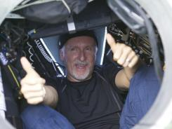 In an image provided Monday by National Geographic, filmmaker James Cameron gives two thumbs-up as he emerges from the Deepsea Challenger submersible.