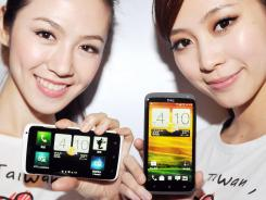 "Models display the HTC ""One"" series."