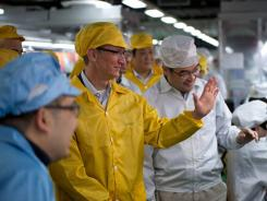 Apple chief executive Tim Cook (in yellow) visiting the iPhone production line at a newly built Foxconn manufacturing facility.