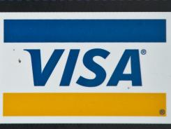 A Visa credit card logos is seen in a store window in Washington.