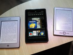 The line of Amazon Kindle products, from left, Kindle Touch, Kindle Fire tablet and the upgraded Kindle, are displayed at a press conference in New York. A new survey finds one in five Americans say they have recently read an e-book in the past year.