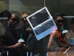 A MacBook Air is displayed in the window of an Apple Store.