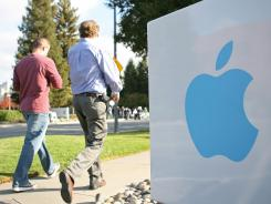 Apple employees walk towards the Apple Headquarters in Cupertino, Calif.