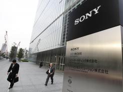 Office workers leave the headquarters of Sony in Tokyo on Tuesday.