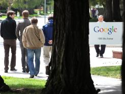 Google workers walk outside of Google headquarters in Mountain View, Calif.