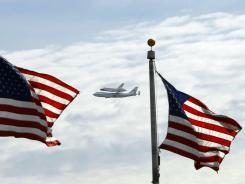 Space shuttle Discovery, mounted on the Shuttle Carrier Aircraft, flies behind flags of the Washington Monument on Tuesday.