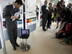 A spectator moves out of the way as Mark-Andre Duc, seen on the computer screen, directs a robot at Switzerland's Federal Institute of Technology in Lausanne, Switzerland.