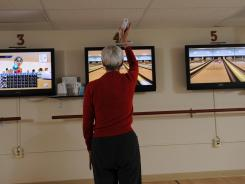 A woman plays Wii bowling.