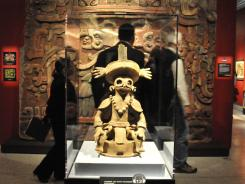 A Censer lid statue of Copan's founder stands in front of a replica mural wall from his pyramid tomb.