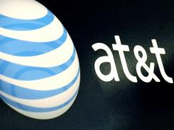 The AT&T logo is on display at a RadioShack store in Gloucester, Mass. AT&T will start selling home automation and security services nationwide.